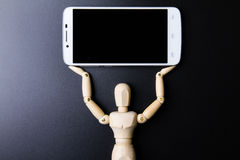 White smartphone and wooden man concept on dark background. Stock Photography