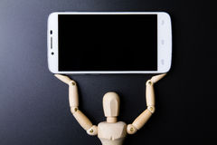 White smartphone and wooden man concept on dark background. Royalty Free Stock Images