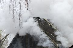White smoke comes from the burning roof of the house. White thick smoke comes from the burning roof of the house royalty free stock photo