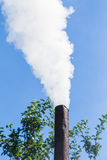 White smoke comes from the chimney on background of blue sky. Air pollution and the environment. The greenhouse effect Stock Photos