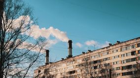 White smoke coming out pipes in town dormitory area on winter sunny day. White smoke coming out water heating station pipes in town dormitory area with multi stock footage