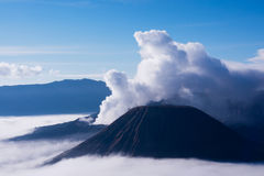 White smoke coming out of volcanoes surrounded by white clouds of mist. White smoke coming out of volcanoes surrounded by white clouds of mist and a clear blue Royalty Free Stock Photo