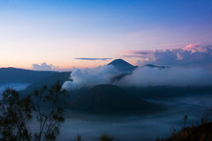 White smoke coming out of volcanoes surrounded by white clouds of mist and a clear blue sky. White smoke coming out of volcanoes surrounded by white clouds of Stock Photos