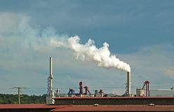 Smoke escaping through the chimney of a factory. White smoke escaping hrough the chimney of a factory into the sky royalty free stock photos