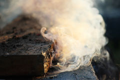 White smoke from the fire where wet boards and sawdust lie. Royalty Free Stock Images