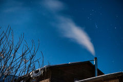 White smoke from the house chimney at the winter night sky backg Stock Photos