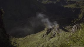 White smoke rising up from crater. Of volcano on background of mountains and rocks. Slow motion. Batur mount, Bali, Indonesia stock video footage