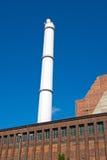 White smokestack and red brick building stock photos