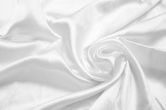 White smooth satin background. Silky smooth white satin background with shine, folds, creases and copyspace Royalty Free Stock Photos