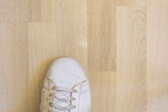 White sneaker shoe on wooden floor Royalty Free Stock Photos