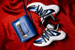 White sneakers with black and blue inserts on a thick figured sole and a blue bag with a gold chain on a red woven background stock photo