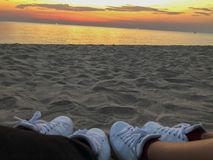 The white sneakers of couple with sunset background on the beach stock images
