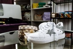 White sneakers decorated with stars of sequins, a checkered belt and a purse on a glass table against the background of shelves royalty free stock photos