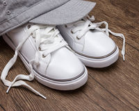 White sneakers with gray cap on dark wooden surface Stock Images