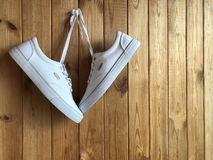 White sneakers hanging on the wall. White sneakers on a wooden background. White sneakers hanging on the wall Royalty Free Stock Images