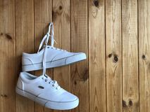 White sneakers hanging on the wooden wall. White sneakers on a wooden background. White sneakers hanging on the wall Royalty Free Stock Image