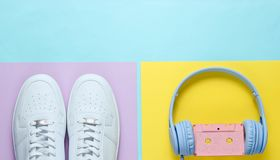 White sneakers, headphones with audio cassette. Retro 80s old fashioned objects on colore background. Top view. Flat lay royalty free stock photos