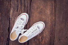 White sneakers. Pair put on an old wooden background Royalty Free Stock Images
