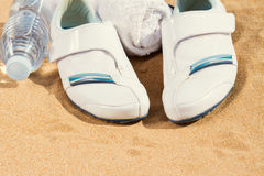 White sneakers in sand Stock Photo