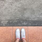 White Sneakers shoes walking on Dirty concrete top view , Canvas shoes walking on concrete Stock Photo