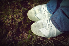 White Sneakers Sport leather shoes walking on moss and grass during sunny day. Stock Photography
