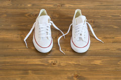 White sneakers standing on the wooden floor. Beautiful white shoes standing on the floor in a dark room Stock Images