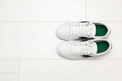 White sneakers on white wooden floor. Royalty Free Stock Photo