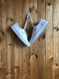 White sneakers on a wood background. White sneakers on a wooden background. White sneakers hanging on the wall Royalty Free Stock Image