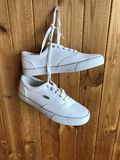 White sneakers on a wooden background. White sneakers hanging on the wall stock photo