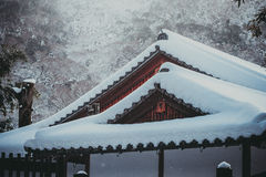 White snow cover on roof of Japanese wooden cottage. Royalty Free Stock Photos