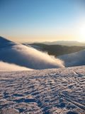 White snow covered mountain peaks on high. Mist flows over the mountain. Deserted blue extreme winter landscape royalty free stock image