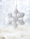 White Snow flake. Bright Snow flake on defocused white background with bokeh Royalty Free Stock Images