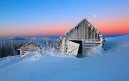 The white snow glows the color of the sky. The old huts stand in the valleys. Cold winter day. The incredible landscape with the sunrise high in the mountains Stock Images