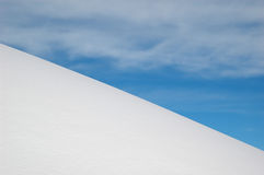 White snow slope, blue sky and white clouds Stock Image
