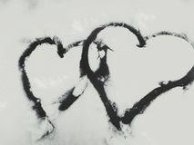 Two hearts painted on the snow stock photo
