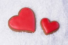 On white snow two gingerbread cookies in the shape of red hearts, copy space, christmas concept and family holiday royalty free stock photos