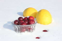 On the white snow, two lemons and a bowl of plums Royalty Free Stock Photography