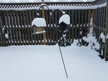White snow on wood fence and bird feeders. White snow and ice on wooden fence and bird feeders royalty free stock photo