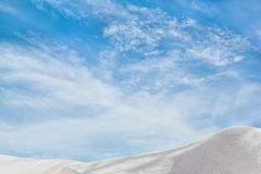 White snowdrift on a background of blue sky with clouds Stock Photography
