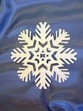 White snowflake. On shining blue satin Royalty Free Stock Photography