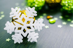White snowflake on background of gold and green xmas baubles. Royalty Free Stock Images