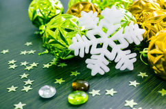 White snowflake on background of green and gold xmas baubles. Stock Photography