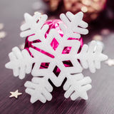 White snowflake on background of magenta and gold xmas baubles. Stock Image