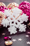 White snowflake on background of magenta and gold xmas baubles. Stock Images