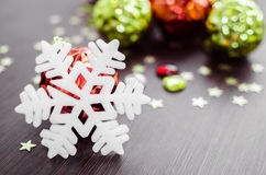 White snowflake on background of red and green xmas baubles. Royalty Free Stock Image