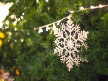 White snowflake on Christmas tree green color decoration by new year`s lighting with bokeh background stock photo