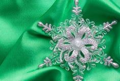 White snowflake on green background. White snowflake on green cloth Stock Photos