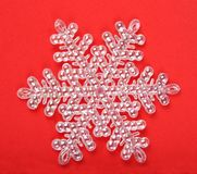 White snowflake on red background Stock Photos