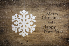 White snowflake star hanging over a rustic wooden background Stock Images