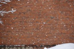 White snowflakes background on blurred unfocused brick wall texture copy space.  stock photography